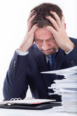 Too Much Work  Portrait of exhausted businessman sitting at office desk full with papers  Standard-Bild