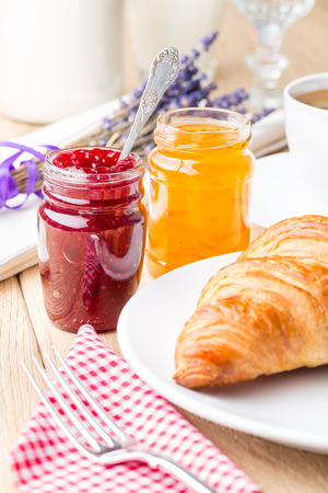 Raspberry and orange jam with croissant  Shallow depth of field