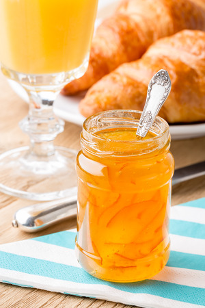 Orange jam with juice and croissants  Shallow depth of field