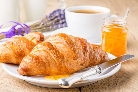 Francese cornetti per la colazione con marmellata d'arancia e caff� profondit� di campo