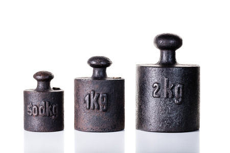 antique weight scale: Vintage iron weights on the white background  Stock Photo