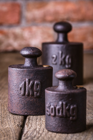Vintage iron weights in front of an old brick wall  Standard-Bild