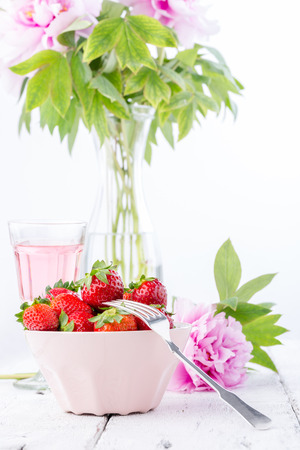 Strawberries in a pink bowl with blooming peony