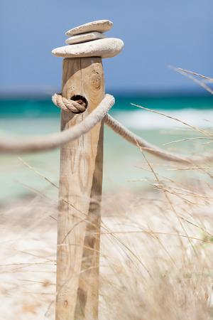 Pietre in equilibrio su ringhiera in legno nei pressi dell'isola Trucadors spiaggia di Formentera, Spagna Archivio Fotografico