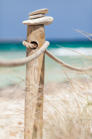 Stones balanced on wooden banister near the Trucadors beach  Formentera island, Spain