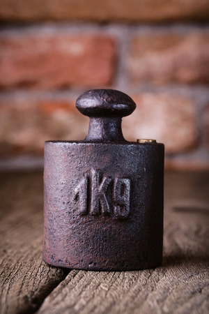 Vintage iron 1 kg weight in front of an old brick wall