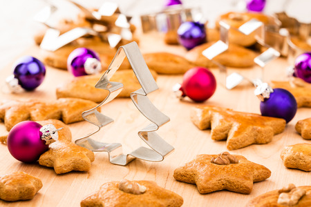 Christmas gingerbread cookies with cutters and christmas baubles. Shallow depth of field. Standard-Bild