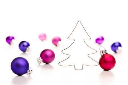 Christmas tree and baubles. Gingerbread cookie cutter and colorful christmas baubles. Shallow depth of field. Stock Photo