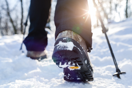 walking boots: Winter hiking. Lens flare, shallow depth of field.