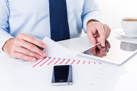 Businessman working on a digital tablet and analyzing column charts. Stock Photo