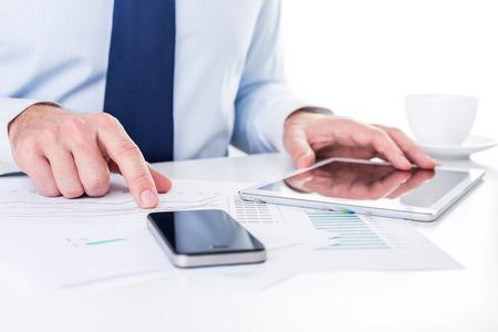 Businessman lavorando su una tavoletta digitale e analisi dei grafici.