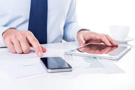 Businessman working on a digital tablet and analysing charts. Stock Photo