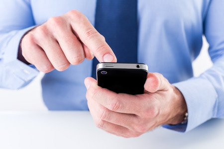 Close up of a businessman hands using smart phone. Shallow depth of field.