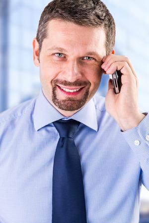 Uomo d'affari sorridente che fa una telefonata nel suo ufficio. Archivio Fotografico