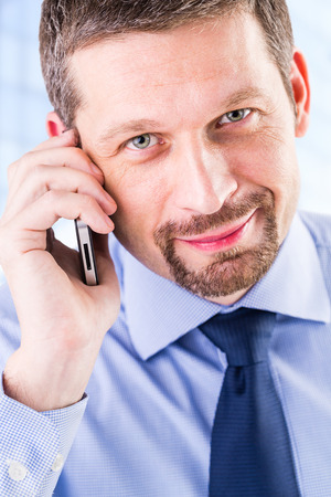 Smiling businessman making a phone call. Stock Photo