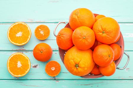 citricos: Naranjas y Mandarinas en colador retro. Foto de archivo