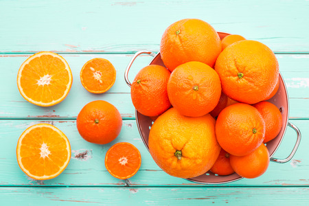 Oranges and Tangerines in retro colander. Stock Photo