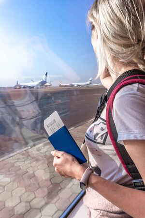 Young woman in the airport, looking through the window at planes.