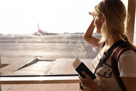 Young woman in the airport, looking through the window at planes, holding a passport with a ticket.