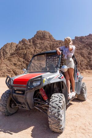 Young happy woman in buggy during safari trip in desert