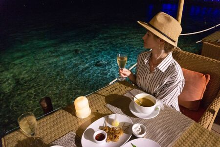 Young woman have romantic evening with candles on sea beach,holds wine