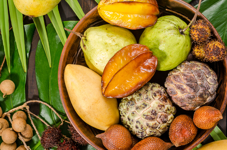 Summer detox with vegan food. Assorted Thai tropical fruits on a dark wooden rustic background. Imagens