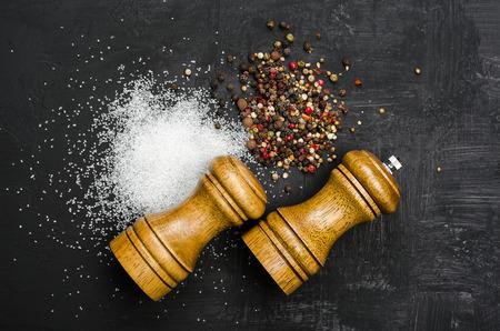 Wooden salt and pepper shaker. Seasoning salt and pepper on black chalk board. Menu cover. Stock Photo
