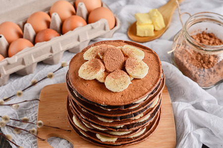 Pancake cake. A stack of chocolate pancakes with chocolate cream and almonds on top.