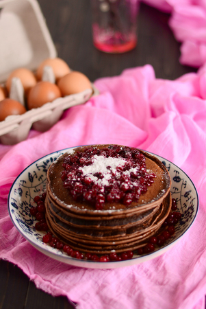 Stack of fried pancakes on a white plate. Chocolate, berries, raspberries, cranberries and blackberries on top. Gray concrete table, vintage forks, cup of tea with brown sugar, teapot.