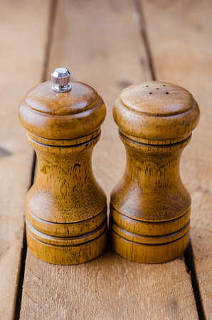 Wooden salt shaker and pepperbox on a wooden rustic background.