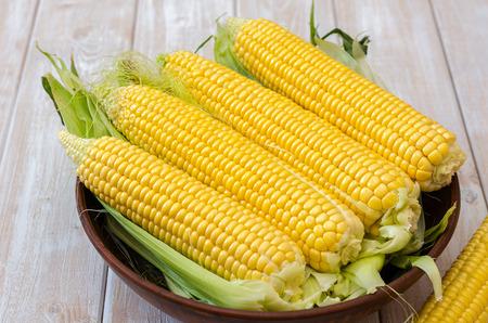 Rijpe maïs in een kleikom op een lichte houten ondergrond.