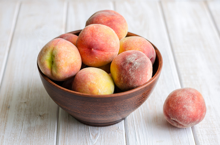 Ripe peaches in a clay dish on a light rustic background.