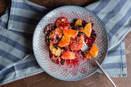 Salad of red orange, beet, orange, ground almonds, dried prunes, honey sauce. Archivio Fotografico