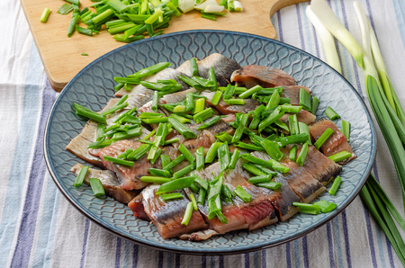 Herring fillet sliced into chunks with green onions on a blue plate. Light wood background. Imagens