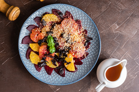 Salad of red orange, beet, orange, ground almonds, dried prunes, honey sauce. Banque d'images