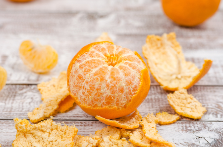 Peele dripe tangerines on wooden light background