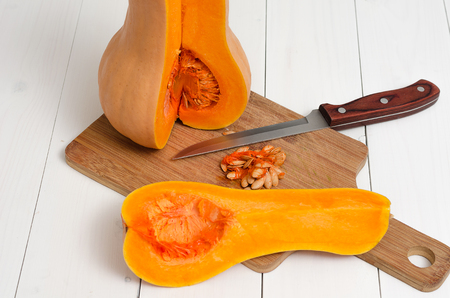 Cut pumpkin on cutting board on white wooden background.