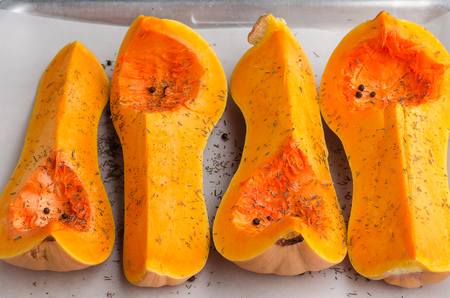 Sliced pumpkin on baking tray, on white wooden background.