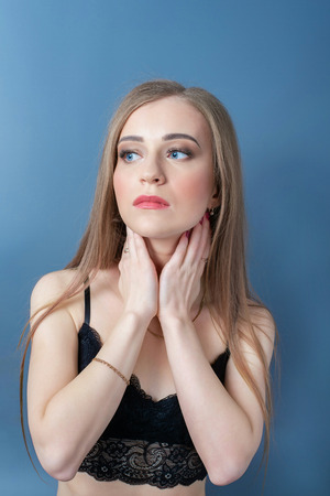Young beautiful girl in black bustier with hands on neck looking up to the left. Blue background.