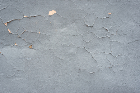 Gray shabby textural background. Cracked paint wall.