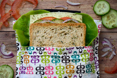 Eco-friendly durable reusable sandwich bag with healthy vegetables on a wooden cutting board. Top view Stock Photo