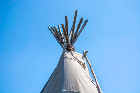 Top of a traditional Native American wigwam lodge or teepee tent against clear blue sky background.