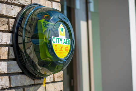 Green automated external defibrillator CITY AED on the street in the city. AED CPR rescue kit box with instruction in Dutch saying how to open lid. Medical device to deliver an electrical shock. Foto de archivo