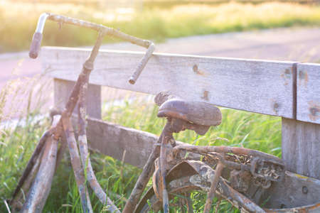 An old abandoned rusty bike parked against a wooden fence. Old fashioned classic bicycle stands forgotten along a bicycle path. 版權商用圖片