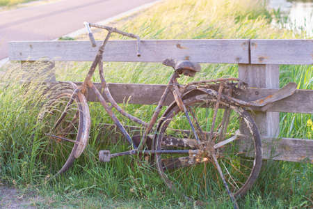 An old abandoned rusty bike parked against a wooden fence. Old fashioned classic bicycle stands forgotten along a bicycle path.