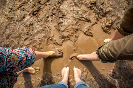 Walking barefoot through muddy road in nature. Barefoot trail. Shoeless womens legs. Grounding, or earthing, making contact with the earth.