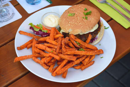 Healthy vegetarian burger with sweet potato fries served with some lettuce on a plate.