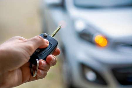 Women hand hand holding contactless car key and pressing the button on the remote to lock or unlock the car. Flashing lights of the car in the background.