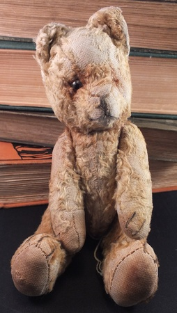 single old teddy bear sat in front of old books Stock Photo - 13272023