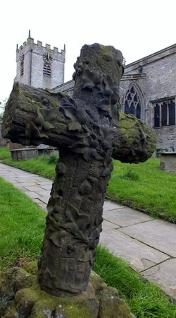 christian halloween: Stone cross gravestone in church yard